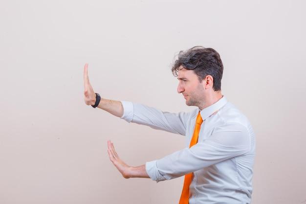 Junger mann hält sich präventiv die hände in hemd, krawatte und sieht genervt aus