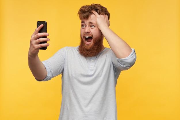 Junger mann, hält smartphone und berührt seinen kopf mit einem verwirrten, verwirrten gesichtsausdruck, der in anzeige zeigt