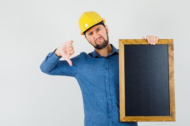 Junger mann hält tafel, zeigt daumen nach unten in hemd, helm und schaut unzufrieden, vorderansicht.