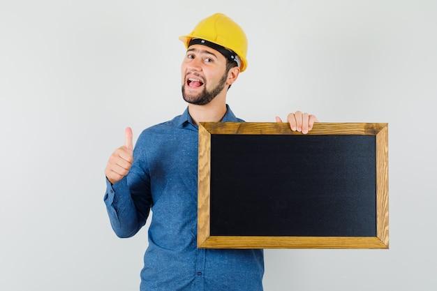 Junger mann hält tafel, zeigt daumen oben in hemd, helm und sieht fröhlich aus. vorderansicht.