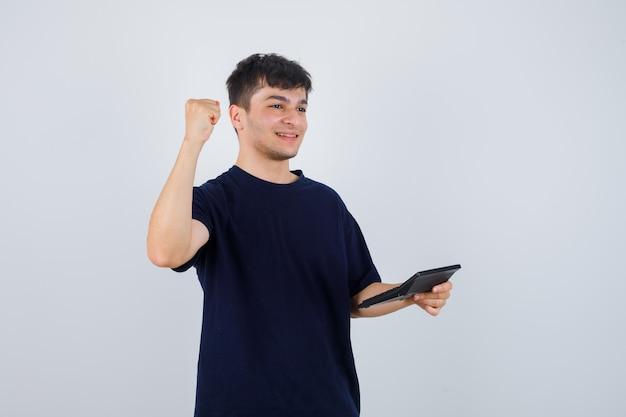 Junger mann hält taschenrechner, zeigt siegergeste im schwarzen t-shirt und schaut glücklich. vorderansicht.