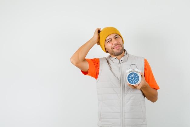 Junger mann hält wecker, kratzt den kopf in t-shirt, jacke, hut und sieht vergesslich aus. vorderansicht.