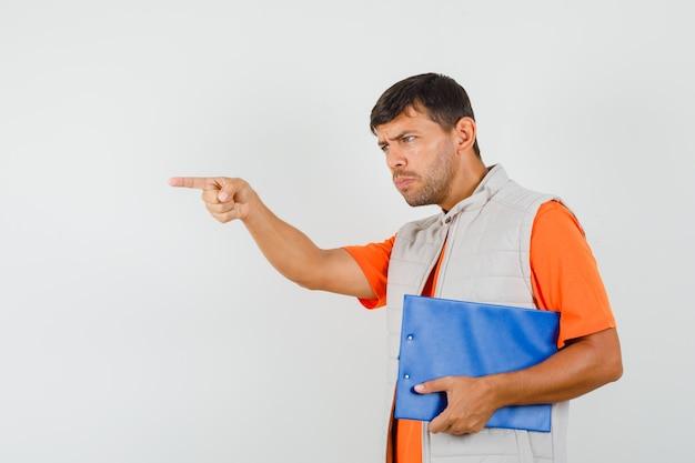 Junger mann hält zwischenablage, gibt anweisungen in t-shirt, jacke und schaut konzentriert. vorderansicht.