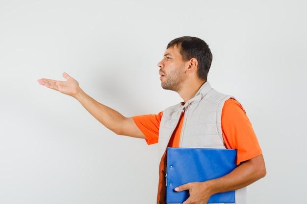 Junger mann hält zwischenablage, stellt fragenzeichen in t-shirt, jacke und schaut verwirrt