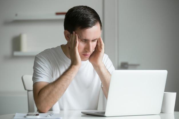 Junger mann, hände an seinen schläfen, am weißen schreibtisch, laptop in der nähe