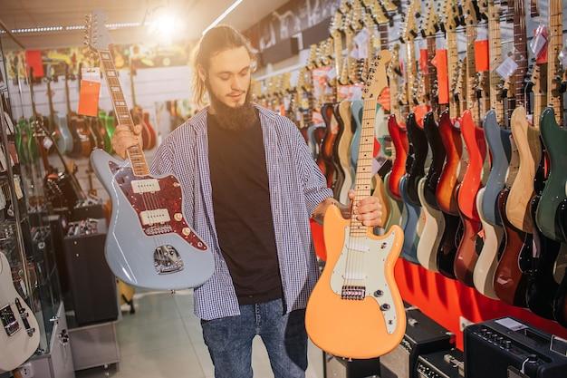 Junger mann halten zwei bunte e-gitarren. er sieht einen gelben an. viele andere e-gitarren stehen hinter ihm. er steht allein im msuic-laden.