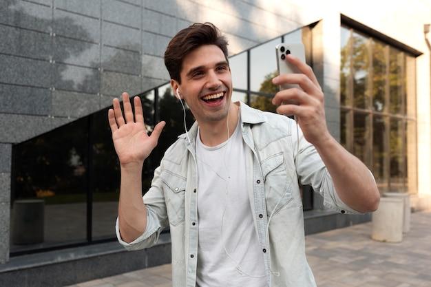 Junger mann hat einen videoanruf auf seinem smartphone