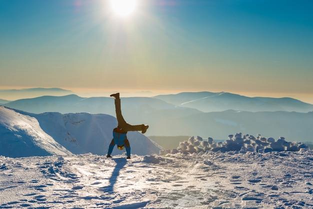 Junger mann hat spaß im schnee in den bergen