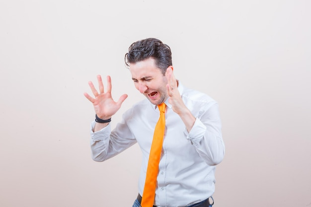 Junger mann hebt aggressiv die hände in weißem hemd, krawatte und sieht aufgeregt aus