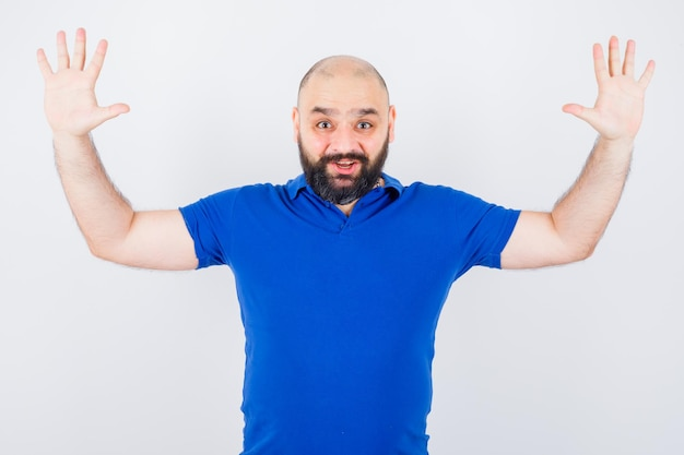 Junger mann hebt die hände im blauen hemd und sieht glücklich aus, vorderansicht.