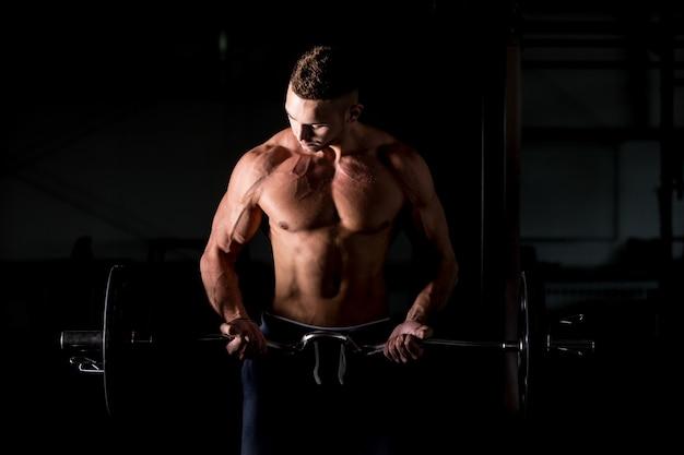 Junger mann hebt eine hantel im fitnessstudio