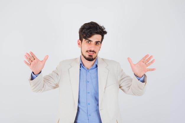 Junger mann hebt hände in kapitulationspose in blauem t-shirt und weißer anzugjacke und sieht fröhlich aus