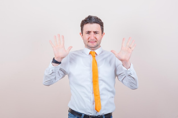 Junger mann hebt handflächen in kapitulationsgeste im weißen hemd
