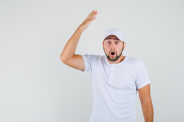 Junger mann hebt seinen arm mit offener handfläche im weißen t-shirt und sieht erstaunt aus. vorderansicht.