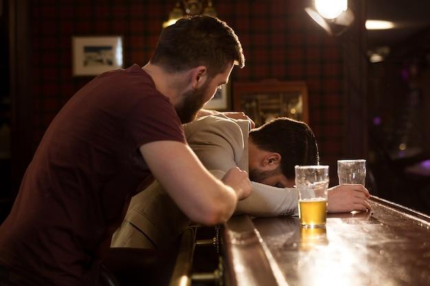 Junger mann hilft seinem betrunkenen freund