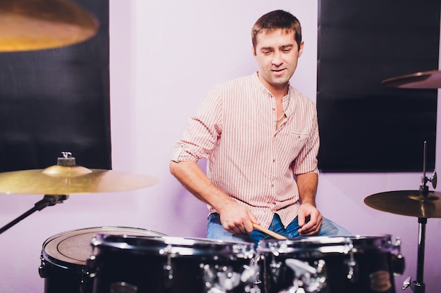 Junger mann hinter trommelinstallation in einem professionellen aufnahmestudio.