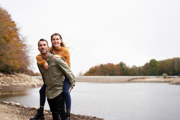 Junger mann huckepack seine freundin und lacht über den see