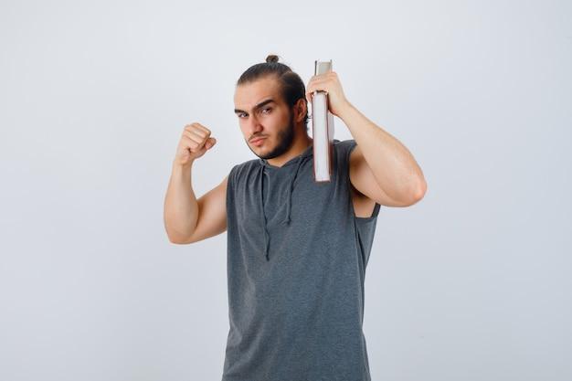 Junger mann im ärmellosen kapuzenpulli, der buch auf schulter hält, während in kampfhaltung steht und ernsthafte vorderansicht schaut.