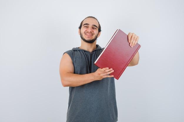 Junger mann im ärmellosen kapuzenpulli, der buch hält, während er posiert und glücklich schaut, vorderansicht.