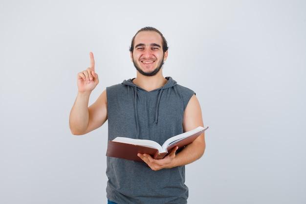 Junger mann im ärmellosen kapuzenpulli, der buch hält, während er zeigt und glücklich schaut, vorderansicht.