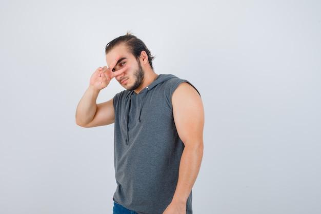 Junger mann im ärmellosen kapuzenpulli, der v-zeichen auf auge zeigt und ernsthafte vorderansicht sieht.