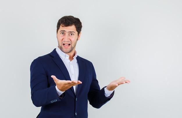 Junger mann im anzug, der hände hält, das missverständnis ausdrückt und verwirrt, vorderansicht schaut.