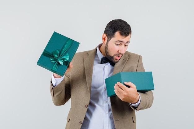 Junger mann im anzug, der in geschenkbox schaut und erstaunt, vorderansicht schaut.
