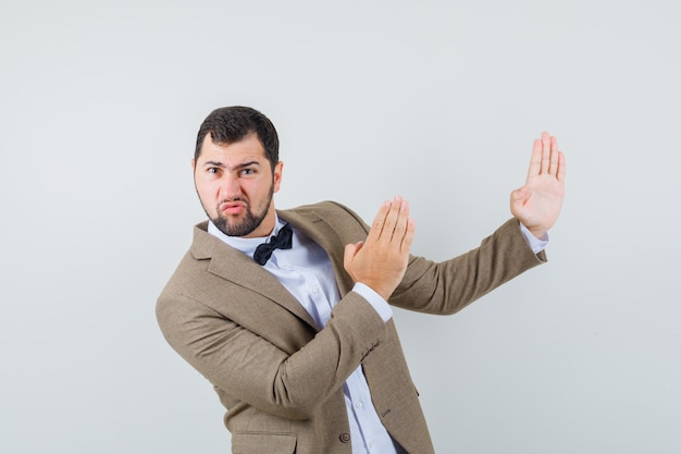 Junger mann im anzug, der karate-hieb-geste zeigt und mächtige vorderansicht schaut.