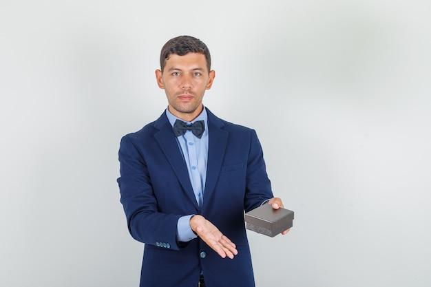 Junger mann im anzug, der uhrenkasten hält und froh schaut