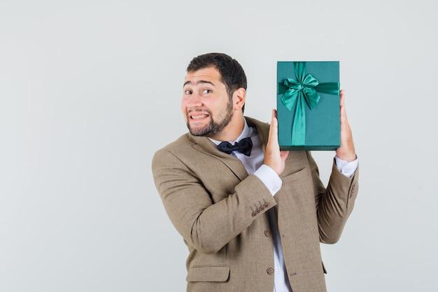 Junger mann im anzug hält geschenkbox und schaut glücklich, vorderansicht.