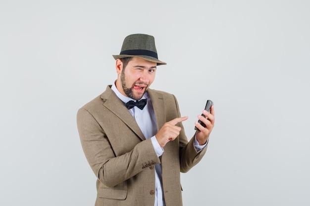 Junger mann im anzug, hut, der berechnungen auf taschenrechner macht und amüsiert, vorderansicht schaut.