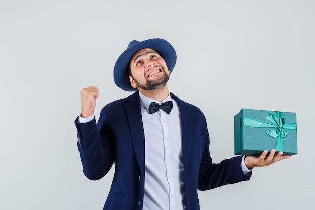 Junger mann im anzug, hut hält geschenkbox mit erfolgsgeste und sieht fröhlich aus, vorderansicht.