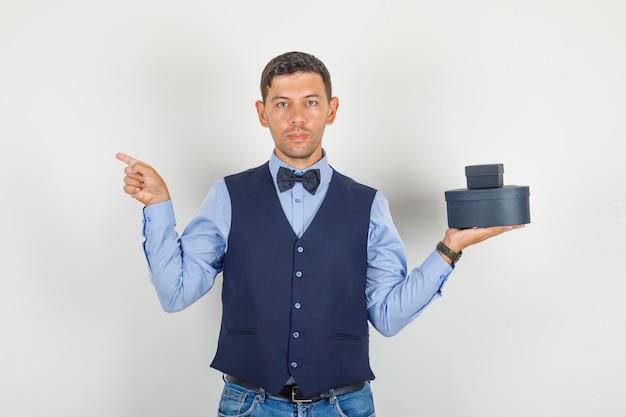 Junger mann im anzug, jeans zeigen weg und halten geschenkboxen