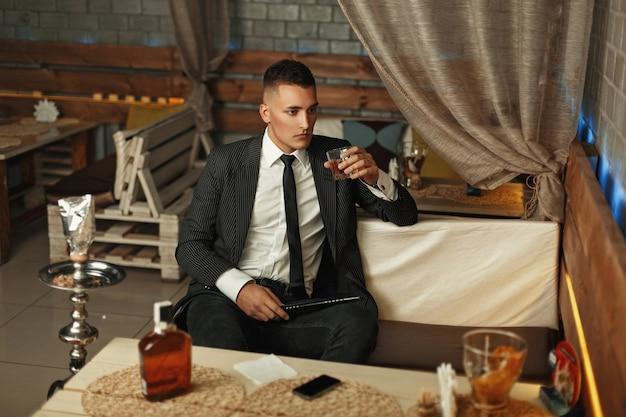 Junger mann im anzug trinkt alkohol und raucht eine wasserpfeife