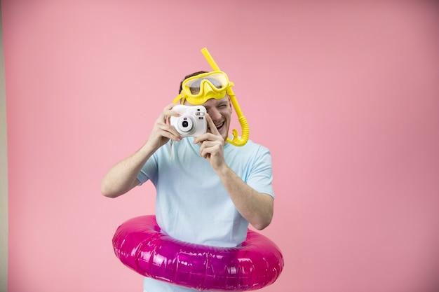 Junger mann im aufblasbaren schwimmring mit schnorchelmaske und schlauch, der foto macht