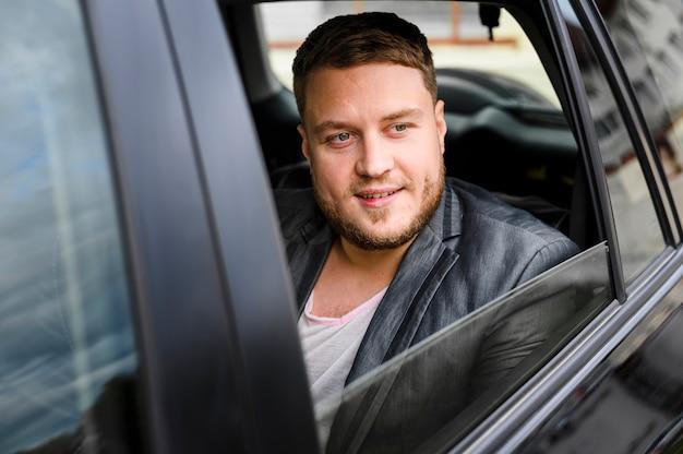 Junger mann im auto mit offenem fenster