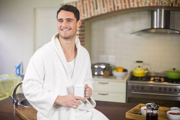 Junger mann im bademantel, der auf küchenarbeitsplatte sitzt und eine tasse tee trinkt