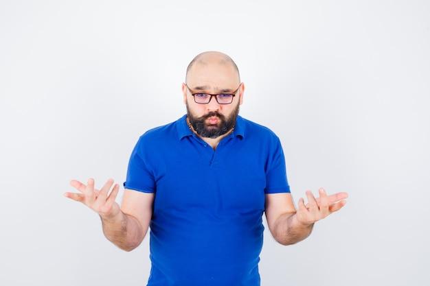 Junger mann im blauen hemd, brille mit hilfloser geste, vorderansicht.