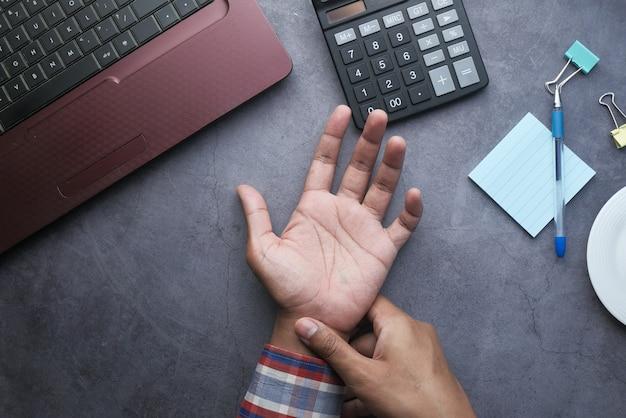 Junger mann im blauen hemd, das handgelenksschmerzen leidet