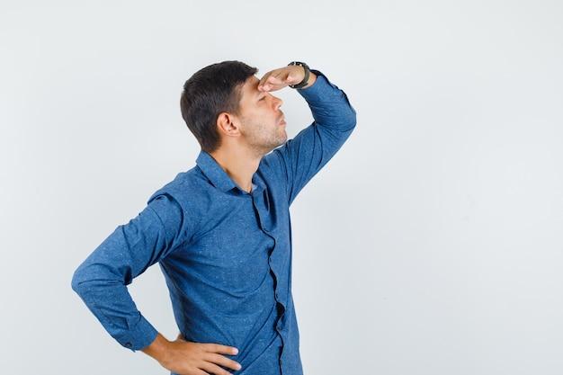 Junger mann im blauen hemd, das mit der hand über dem kopf weit weg schaut, vorderansicht.