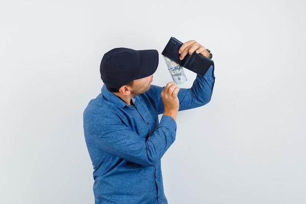 Junger mann im blauen hemd, mütze, die dollarnote aus der brieftasche nimmt und fokussiert aussieht, vorderansicht.