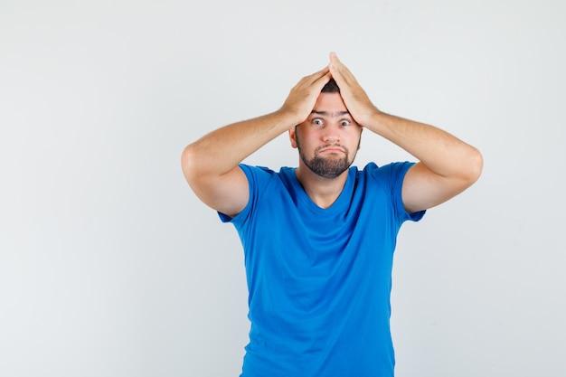 Junger mann im blauen t-shirt, das hände auf kopf hält und verlegen aussieht