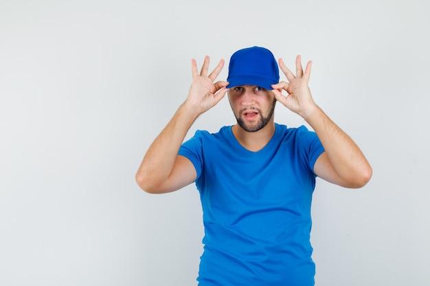 Junger mann im blauen t-shirt, das seine mütze herunterzieht und cool aussieht