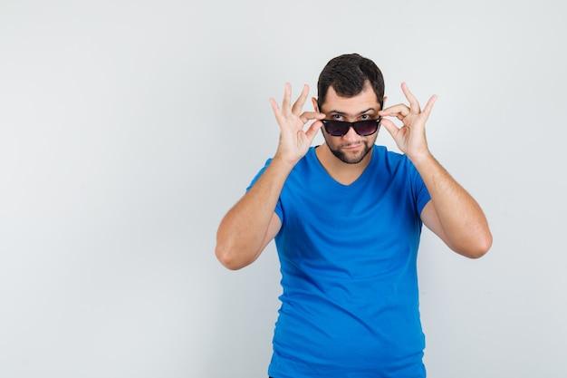 Junger mann im blauen t-shirt, das über brille schaut und konzentriert schaut