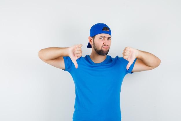 Junger mann im blauen t-shirt und in der kappe, die daumen nach unten zeigen und unzufrieden aussehen