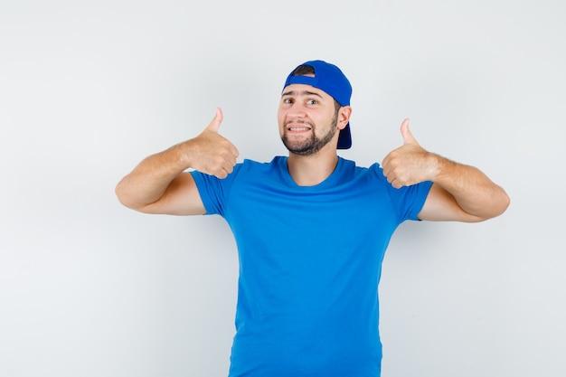 Junger mann im blauen t-shirt und in der kappe, die daumen oben zeigen und erfreut schauen