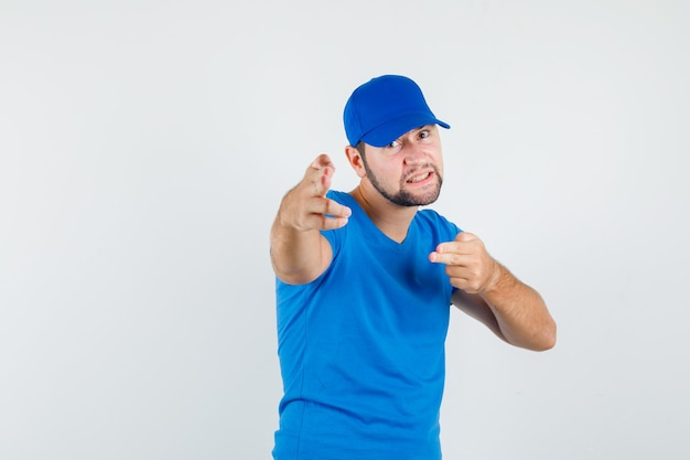 Junger mann im blauen t-shirt und in der kappe, die durch waffengeste auf kamera zeigen und wütend schauen