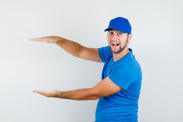 Junger mann im blauen t-shirt und in der kappe, die größenzeichen zeigt und fröhlich schaut