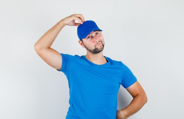 Junger mann im blauen t-shirt und in der kappe, die hand auf kopf halten und zögernd schauen