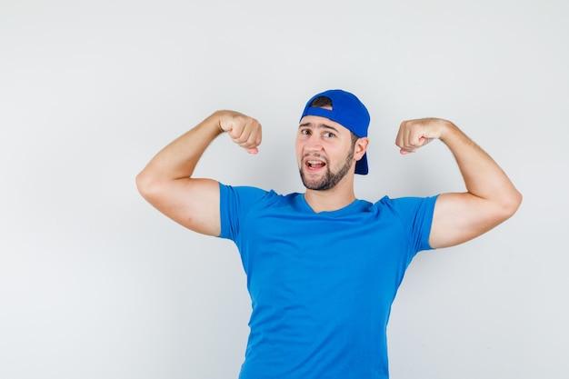 Junger mann im blauen t-shirt und in der kappe, die muskeln der arme zeigen und zuversichtlich schauen